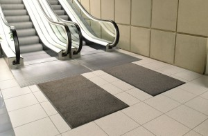 Dark grey mats by escalator